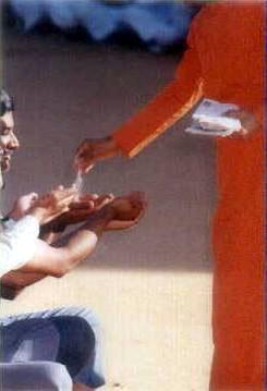 Sathya Sai Baba distributing vibhuthi in darshan